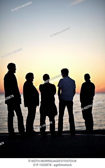 Silhouette of five men standing watching the sunset over Cardigan Bay from the promenade Aberystwth Wales UK