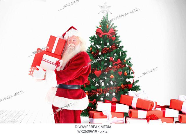 Santa claus holding stack of gift boxes near christmas tree