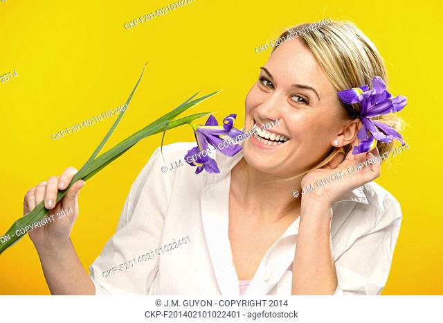 Smiling woman with spring iris flower in her hair