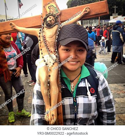 A young female pilgrim holds a sculpture of Jesus Christ during the annual pilgrimage to the Basilica of Our Lady of Guadalupe in Mexico City, Mexico