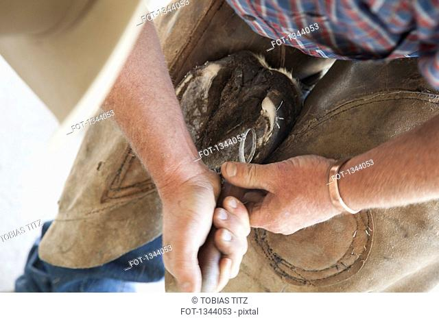 Midsection of man cleaning horse shoe outdoors