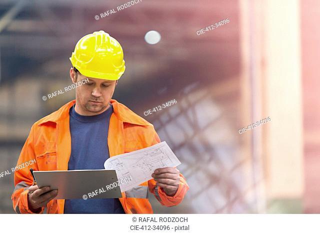 Steel worker reviewing blueprints in factory