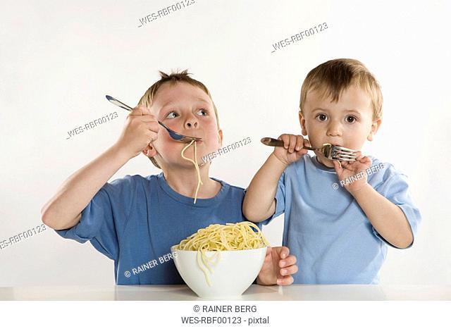 Two boys 6-7 2-3 eating spaghetti, portrait