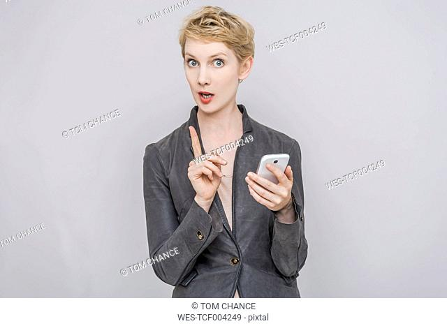 Portrait of blond woman with wagging finger and smartphone in front of grey background