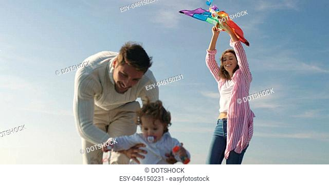 Family with kids resting and having fun at beach during autumn day