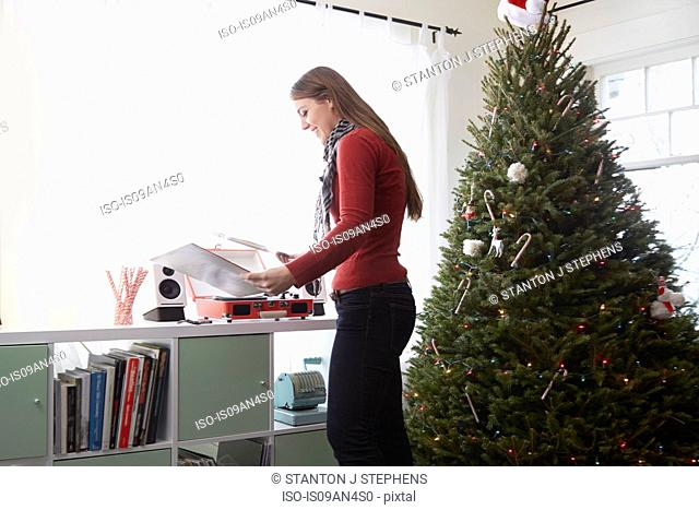 Young woman putting vinyl on record player at christmas