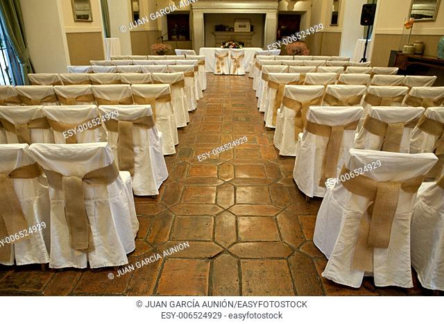 Rows of chairs at a wedding ceremony indoors