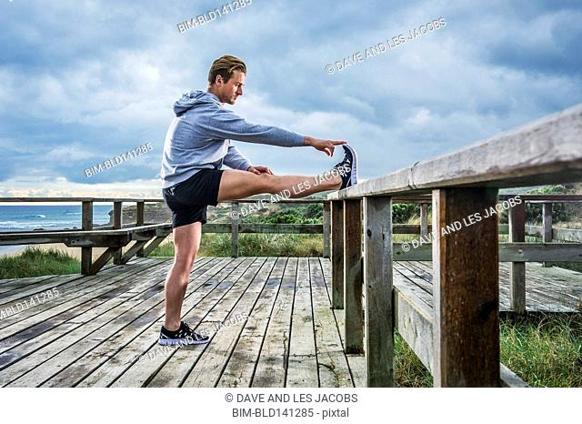 Caucasian runner stretching on wooden boardwalk at beach