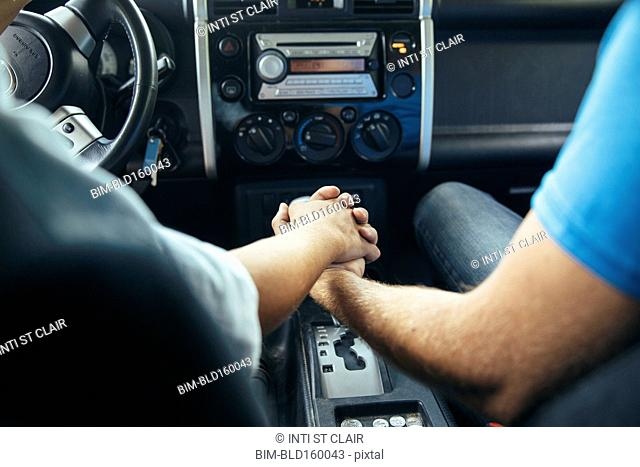 Caucasian couple holding hands in car
