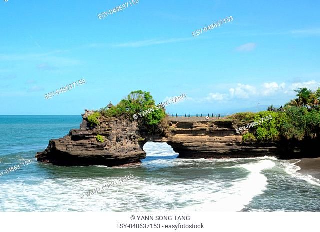 Pura Batu Bolong on the edge of a cliff at coastline with hole in the rock in Bali, Indonesia