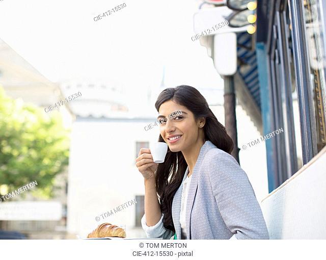 Woman drinking espresso at sidewalk cafe near Sacre Coeur Basilica, Paris, France