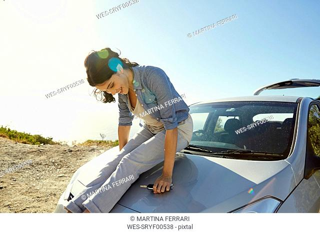 Happy young woman sitting on a car