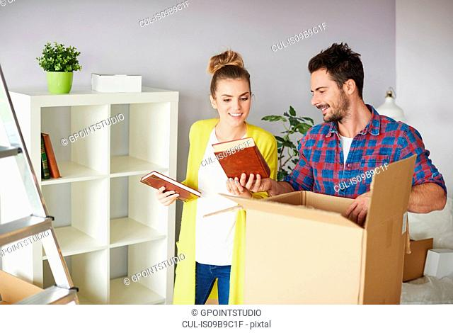 Young couple moving home, packing belongings into cardboard box