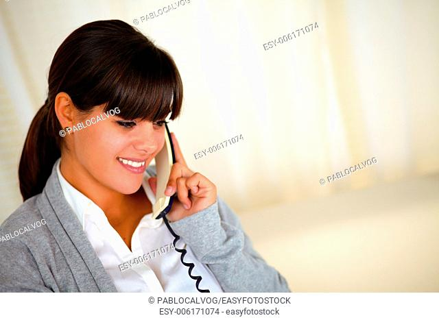 Portrait of a charming latin woman speaking on phone at soft colors composition