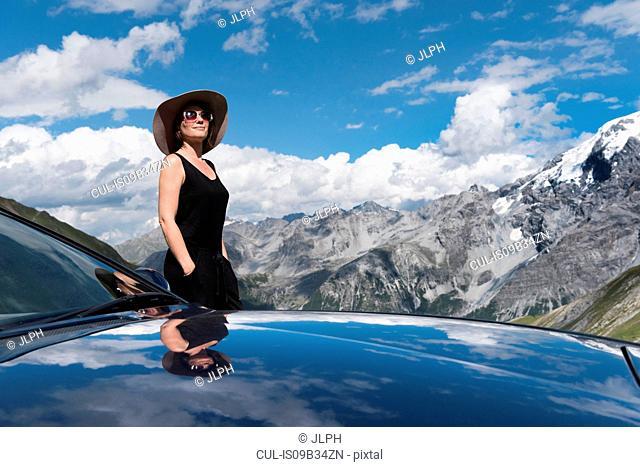 Woman by car in mountains looking away, Passo di Stelvio, Stelvio, Italy