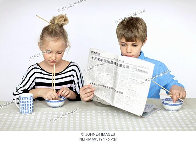 Girl eating with chopsticks and boy reading newspaper