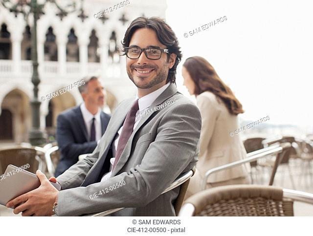 Portrait of smiling businessman holding digital tablet at sidewalk cafe in Venice