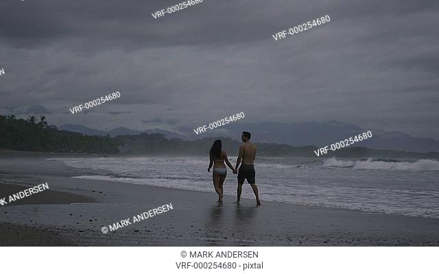 Wide panning shot of couple walking on beach / Esterillos, Puntarenas, Costa Rica