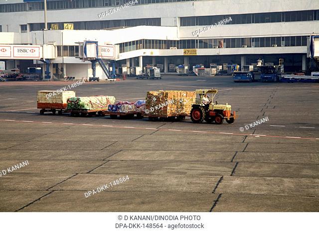 Luggage transport pulled by tractor vehicle on runway at Chattrapati Shivaji Terminal ; Santacruz ; Bombay now Mumbai ; Maharashtra ; India
