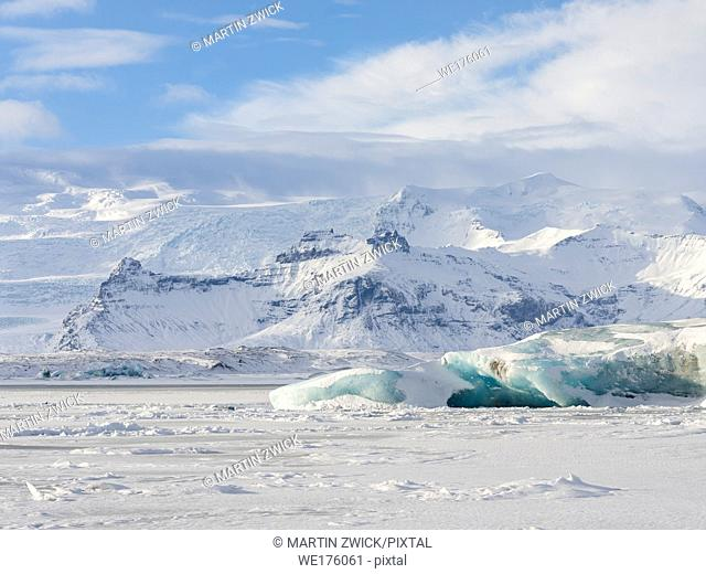Glacial lagoon Joekulsarlon at Breithamerkurjoekull in NP Vatnajoekull during winter. Background summit of Oeraefajoekull, the highest mountain in iceland