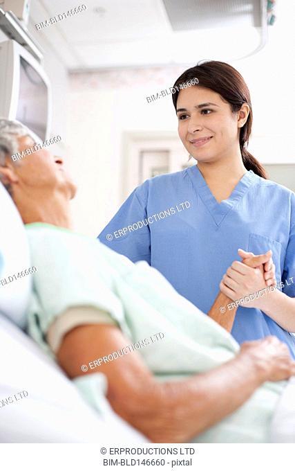 Nurse comforting patient in hospital bed