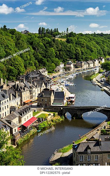 Treed valley riverside town, stone bridge and boats in the harbour with blue sky and clouds; Dinan, Brittany, France