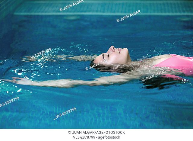 Side view of woman swimming on back in the pool and relaxing with eyes closed. Horizontal indoors shot