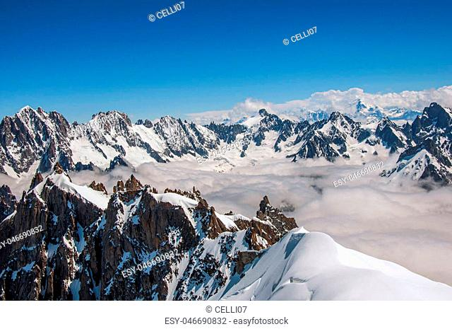 Snowy peaks and mountains in a sunny day, viewed from the Aiguille du Midi, near Chamonix. A famous ski resort located in Haute-Savoie Province