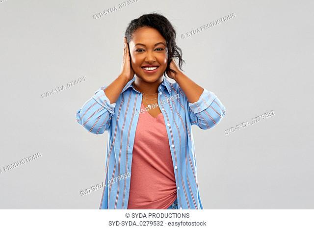happy african american woman closing ears by hands
