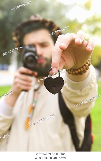 Man recording heart-shaped love lock in his hand with vintage video camera