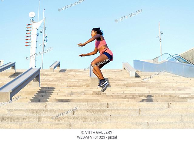 Young woman during workout on stairs, jumping