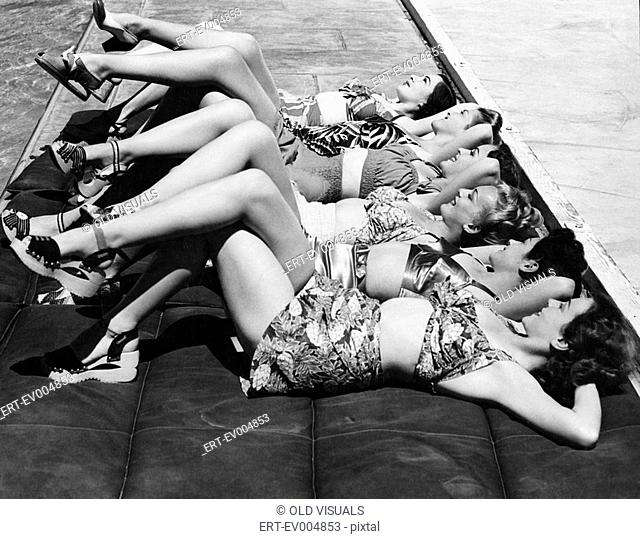 Group of women relaxing in a row together All persons depicted are not longer living and no estate exists Supplier warranties that there will be no model...
