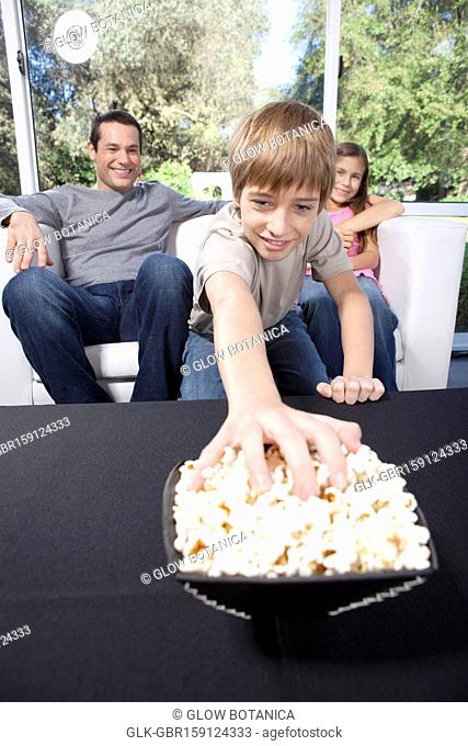 Boy picking bowl of popcorns with his father and sister sitting behind him