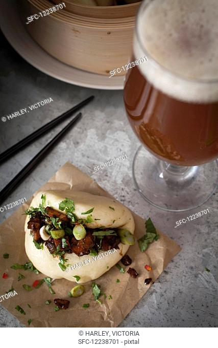 Vegan steamed bao bun filled with smoked tofu and chestnut mushrooms marinated in soy, sesame oil, chilli sauce and garlic, topped with sliced spring onions