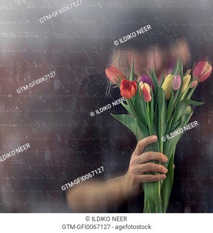 Woman smells a few tulips in her hand
