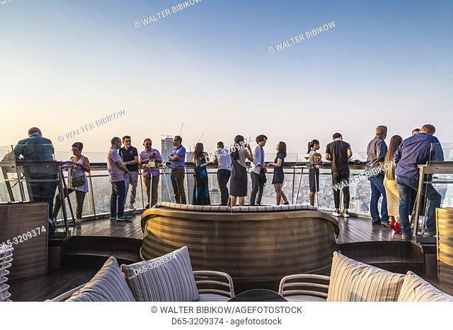 Thailand, Bangkok, Riverside Area, visitors to rooftop bar at The Lebua Hotel, dusk, NR