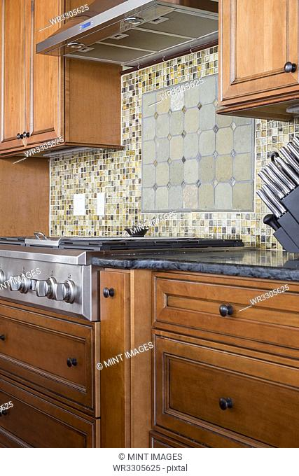 Tile back splash and stove in rustic kitchen