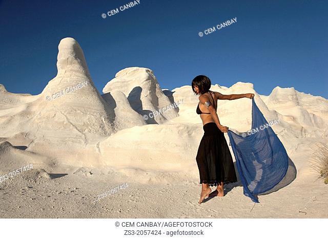 Woman posing near the white rock forms in Sarakiniko beach, Milos, Cyclades Islands, Greek Islands, Greece, Europe