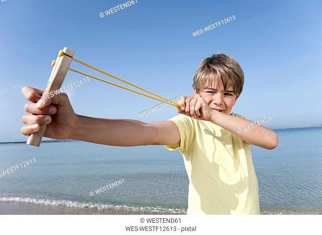 Spain, Mallorca, Boy 8-9 using sling-shot