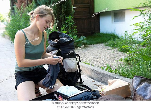 East-Berlin, Germany. Young French backpacker, reorganizing her luggage in front of 'Das Ostel', she stayed in