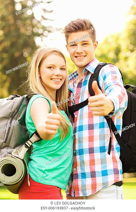 travel, vacation, tourism, gesture and friendship concept - smiling couple with backpacks showing thumbs up in nature