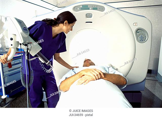 Technician guiding patient into CT scanner in hospital