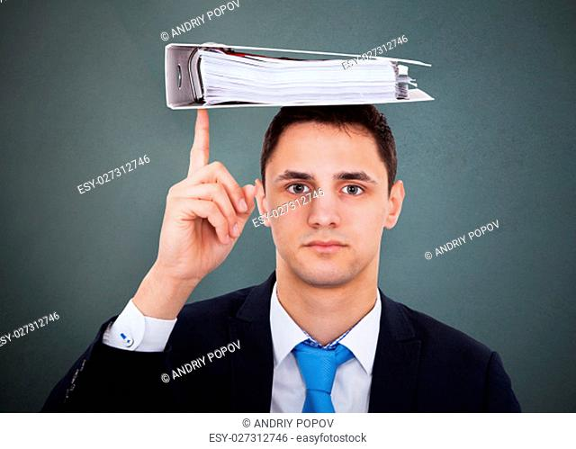 Portrait Of A Young Businessman Balancing Binder On Head On Gray Background