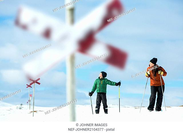 Mother with son skiing