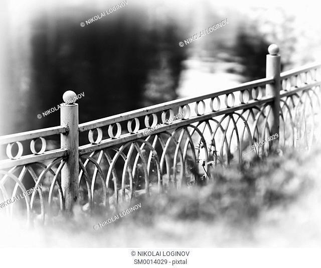 Horizontal diagonal black and white fence in park bokeh vignette background backdrop