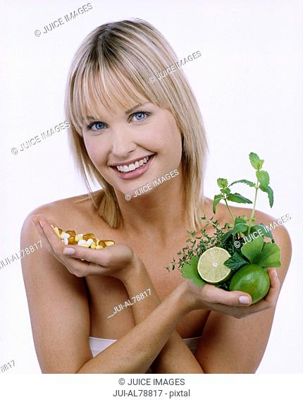 Studio shot of woman with handful of vitamins and fruit