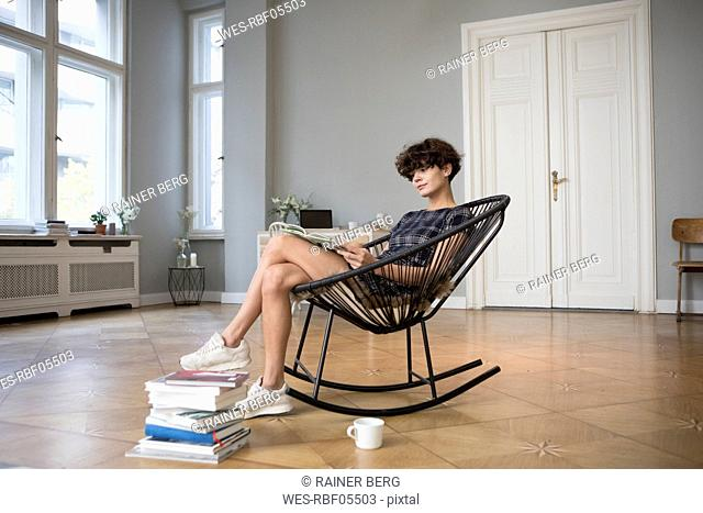 Young woman sitting on rocking chair at home reading a book