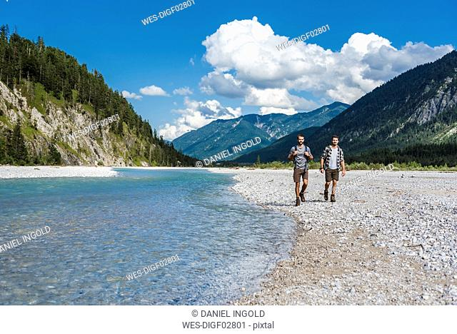 Germany, Bavaria, two hikers walking at riverside