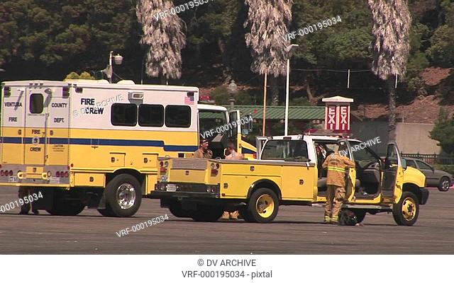 A fire crew exits and walks around their trucks