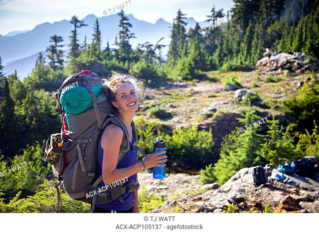 A young woman hiking with backpack to 5040 Peak in the Alberni-Clayoquot region on Vancouver Island, BC, Canada